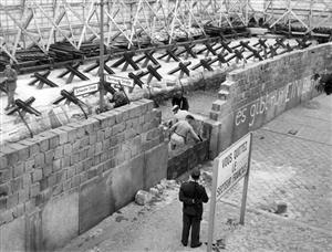 1962年,来自东德的砌墙工人修筑柏林墙,一旁负责守卫的是东德的士兵